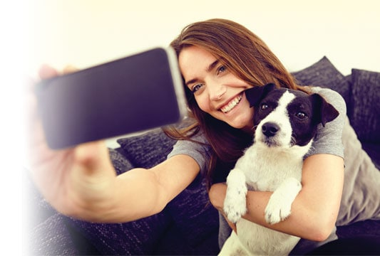 an image of a woman taking a selfie while holding her dog